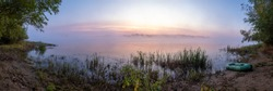 Panorama of the river with fog during sunrise and little inflatable boat on the coast. River of Buzan, Russia