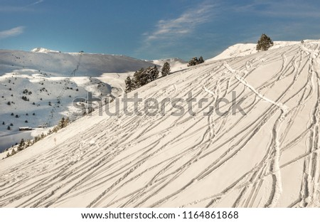 Panorama of the snowy off-piste slope with tracks from snowboarder and skiers and other mountain slopes with chairlift  on background and blue sky with clouds over this landscape (Andorra, sunny day) #1164861868