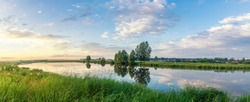 panorama of the summer evening landscape on the Ural river with pine trees on the shore, Russia, June