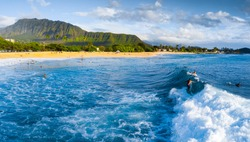 Panorama of the surf spot Makaha with the surfer riding the wave. Oahu, Hawaii