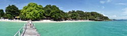 Panorama of the tropical beach resort from Wooden jetty in Ko Samet island, young women walk to the beach, Thailand