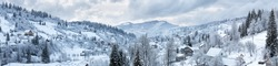 Panorama of the village in the winter mountains covered with snow. Winter landscape. The concept of freedom and solitude.