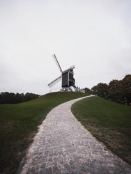 Panorama of trail path to historic traditional Sint Janshuismolen windmill post mill in Bruges West Flanders Belgium