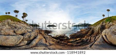 Panorama of tropical coast with beach,  palm trees and island in calm blue sea. Nai Harn beach area of Phuket. Thailand