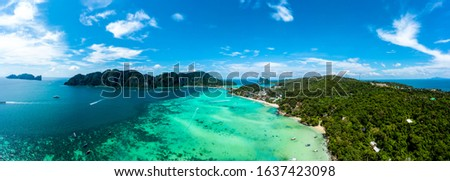 Panorama of tropical islands Phi Phi Don and Phi Phi Leh in sea. Vacation holidays concept background. Aerial view of Tonsai bay with many boats and speedboats above coral reef.  Krabi, Thailand