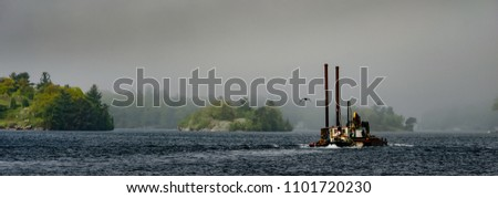 Panorama of Tugboat and barge on the St. Lawrence River passing three fog shrouded islands