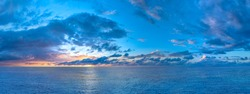 Panorama of twilight sunset over the sea with colorful clouds. Dramatic atmosphere created by the sunlight. Colorful gradient from blue to orange. High resolution panoranic sky.