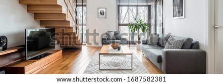 Panorama of two-floor apartment with spacious living room with wooden stairs and hardwood floor