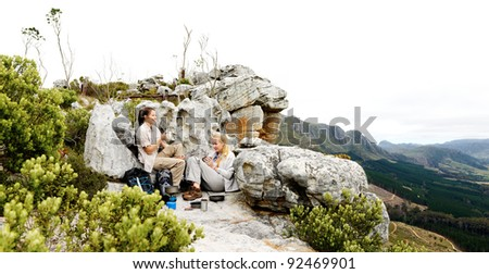Panorama of two friends making camp after a long hike outdoors in the mountains. large file with copyspace ideal for double page spread or billboard use