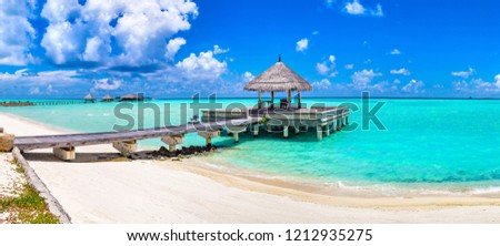 Panorama of Water Villas (Bungalows) and wooden bridge at Tropical beach in the Maldives at summer day #1212935275