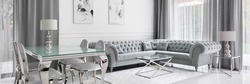Panorama of white and gray living room in glamour style with glass dining and coffee tables and quilted corner sofa