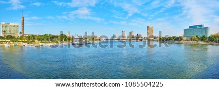 Panorama of wide Nile river with buildings of Cairo Downtown and Gezira Island on the banks, the Bridge of 6th of October is seen on the distance, Cairo, Egypt. #1085504225
