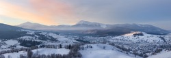Panorama of winter mountains hills at sunrise