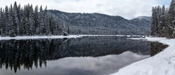 Panorama of Wintry Forest in Mountain Lake