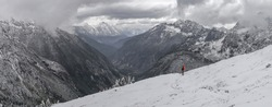 Panorama of young woman carrying orange backpack stands on Cascade Pass trail, on the way to Sahale glacier camp, North Cascades National Park, WA, USA. Concept of solo female traveler.