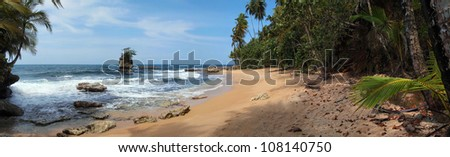 Panorama on a beautiful sandy beach with rocky islet and tropical vegetation, Caribbean sea, Costa Rica