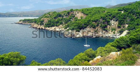 Panorama on rocky coast of the Mediterranean sea with a sailboat, Costa Brava, Catalonia, Spain