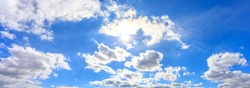 Panorama or panoramic photo of blue sky and white clouds or cloudscape. With sunlight sunbeams or sunrays through the cloud.
