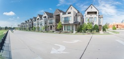 Panorama park side brand new row of three story single family houses in Richardson, North Dallas. Modern design of urban living residences with condominium building construction site in background