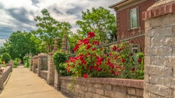 Panorama Pathway along stone and wire fence of ressidential building with red brick wall