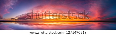 Panorama Reflection of vivid sunset sky over sea.Colorful sunrise with Clouds over ocean.