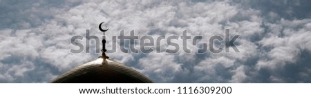 Panorama. Silhouette of the minaret of an Islamic mosque against the background of a cloudy sky. Copy space. For designers of postcards, labels, wallpapers. #1116309200