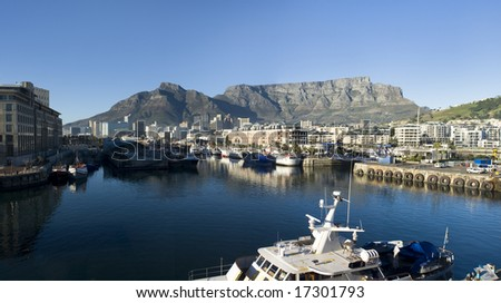 Panorama skyline view of Cape Town, South Africa with the Victoria and Albert harbor and drydocks in the foreground and Table Mountain in the background.