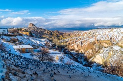 Panorama snowy view of the famous Pigeon Valley in Cappadocia, Turkey with unique fairy chimneys and pigeon houses in winter