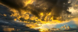 panorama Sunlight with dramatic sky on dark background.Vivid sunset on dark cloud.