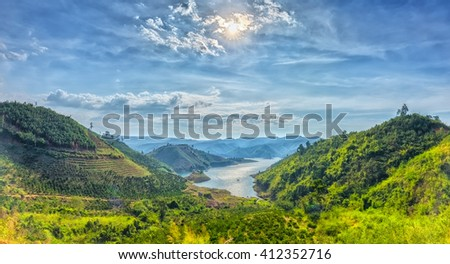 Panorama sunset hillside Ta Dung hydro lake with mountains blue swirled large lake with islands, far away from the real little house idyllic rural countryside scene Vietnam