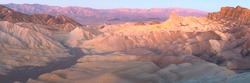 Panorama sunset or sunrise view of Zabriskie Point and the rugged sedimentary rock terrain of the badlands landscape in Death Valley Park National Park, USA.