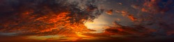 Panorama Sunset with clouds, in orange and colorful shades,World Environment Day concept: Fiery orange sunset sky with dark clouds.