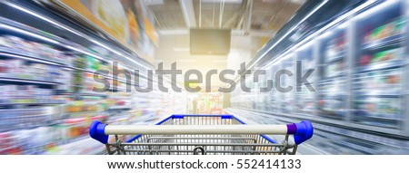 Panorama. Supermarket aisle with empty blue shopping cart