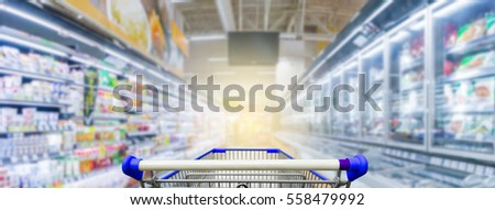Panorama. Supermarket aisle with empty blue shopping cart #558479992