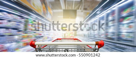 Panorama. Supermarket aisle with empty red shopping cart