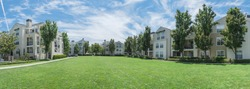Panorama view apartment building complex with grassy backyard in Palo Alto, California, USA. Summer cloud blue sky
