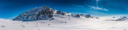 Panorama view at the whole Atoklinten Mountain in Lappland, Northern Sweden, side view. All snowmobiles drive here, many trails around. Bright sunny day, snow, blue skies, much copy space