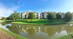 Panorama view mirror reflection of typical riverside apartment building complex in Irving, Texas, USA. Urban eco living place with a lot of mature trees and canal