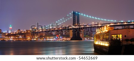 Panorama view. New York City Manhattan skyline with Manhattan bridge and boat at night.