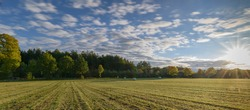 Panorama view of beautiful countryside scene with hay bales in the field after harvest. Rural landscape with mowed field and hay balls in countryside.