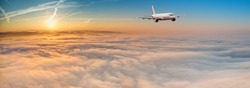 Panorama view of commercial airplane flying above dramatic clouds during sunset.
