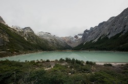 Panorama view of glacier water Emerald Lake i9n the mountaintop, in Ushuaia, Tierra del Fuego Patagonia Argentina. Turquoise color water lake surrounded by the Andes mountains and forest.