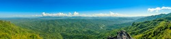 Panorama view of hills and mountain range full of green tree with river through valley and clear blue sky.
