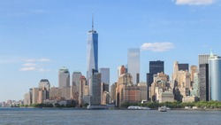 Panorama view of Manhattan, New York City with blue sky and slightly cloud. Battery park on the edge of the shore which surround by many tall building in business area.