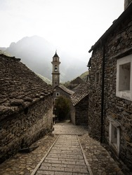 Panorama view of old historic traditional schist stone rock building church clock bell tower in picturesque quaint charming village Sonogno Verzasca Valley Locarno Ticino, Switzerland alps Europe