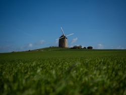 Panorama view of old rustic historic windmill Moulin de Moidrey in green grass field meadow Pontorson Normandy France Europe
