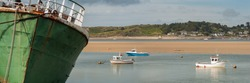 Panorama view of old rusting ship moored on river estuary with snmall boats and village in the background