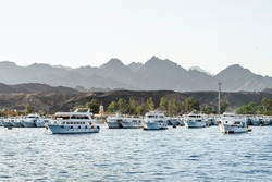 Panorama view of Red sea harbor with many white private yacht. Tourist ships parked at port near mountains. Landscape Egypt Sharm El Sheikh