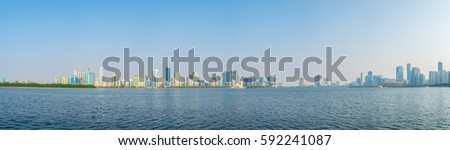 Panorama view of the Khalid lagoon including al Majaz amphitheater surrounded with skyscraper in the emirate Sharjah, UAE #592241087