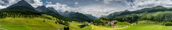 panorama view of the lower Engadin valley near Scuol in the Swiss Alps with the village of Tarasp and its castle in the foreground